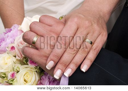 Wedding Rings, Hands And Bouquet Of Roses.