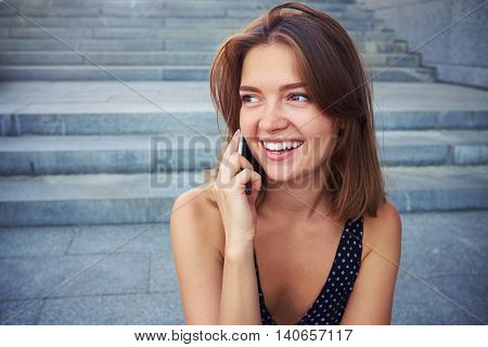 An attractive girl has rather lively conversation on her smart phone while sitting in the street