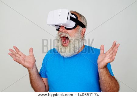 Fit aged man in VR-headset is surprised by the reality of the picture this technology provides isolated against white background