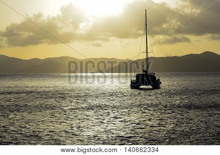Catamaran on the water at sunset with an island in the background.