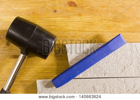 Rubber hammer and chisel on a background of stone cladding