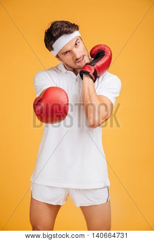 Aggressive young man boxer in red gloves warming up and ready to fight over yellow background