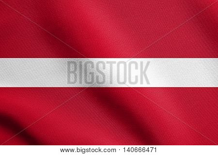 Flag of Latvia waving in the wind with detailed fabric texture. Latvian national flag.