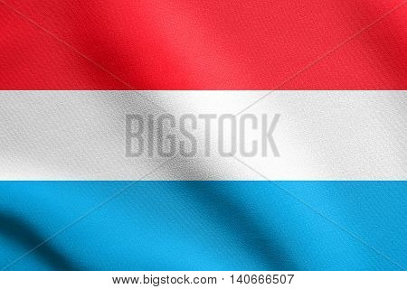 Flag of Luxembourg waving in the wind with detailed fabric texture. Luxembourgish national flag.