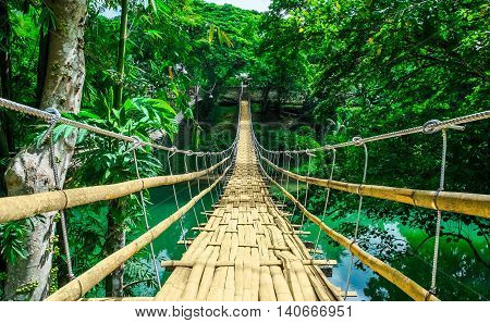 Bamboo pedestrian hanging bridge over river in tropical forest Bohol Philippines Southeast Asia