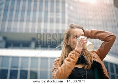 Blonde woman drinking coffee to go