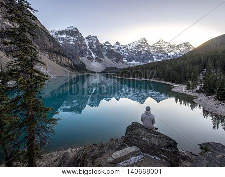 Young man sitting on a rock overlooking a beautful blue mountain lake