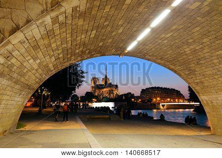 Notre Dame de Paris at dusk viewed under bridge as the famous city landmark.