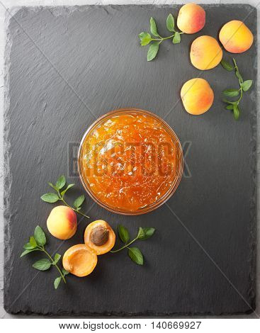 apricot jam in a glass bowl fresh apricots on black stone background (Top view )
