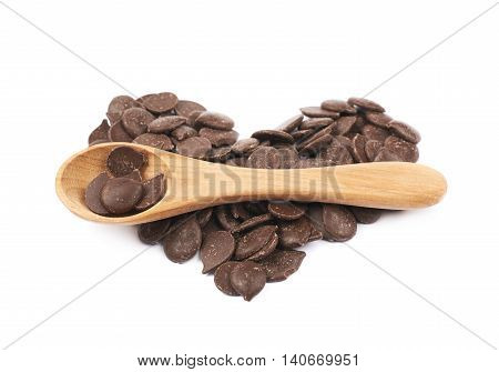 Heart shape made of cooking chocolate teardrop shaped chips with the wooden spoon over it, composition isolated over the white background