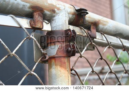 A rusty post and a chain link fence.