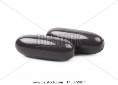 Two black medical drug pills composition isolated over the white background