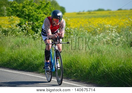 GRAFHAM, CAMBRIDGESHIRE, ENGLAND - MAY 22, 2016:  Close up of Male triathlete  competitor on road cycling stage.