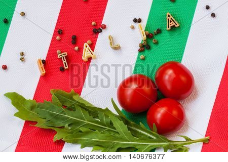 Pasta in the form of letters, arugula, cherry tomatoes on the background of the Italian tricolor