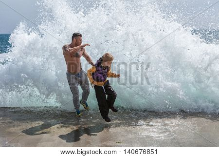 happy father and son who are running away from a wave
