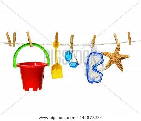 Children's summer toys on clothesline against white background