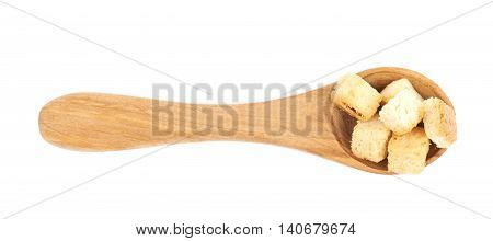 Wooden serving spoon full of white bread garlic croutons isolated over the white background