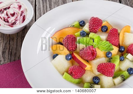 yummi fruit and berry summer dessert salad decorated with mint leaves in white wide rim dish on wooden boards and cream sauce bilberry dip view from above close-up