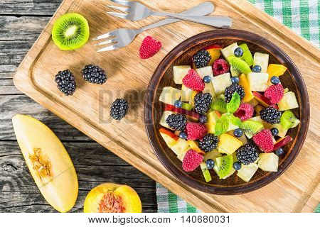 delicious fruit and berry summer salad decorated with mint leaves on clay dish on cutting board with dessert forks half of peach and slice of melon on rustic boards view from above