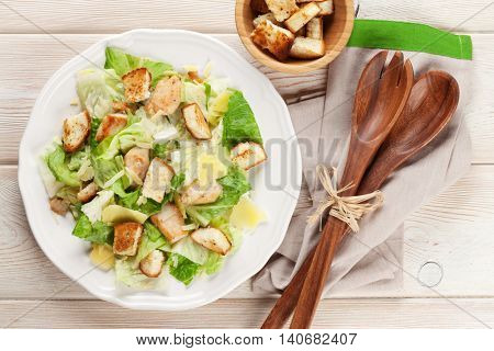 Fresh healthy caesar salad on wooden table. Top view