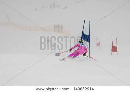 Slalom racer on a low visibility day wearing a pink ski race suit.  Racer is getting very close to the flags.