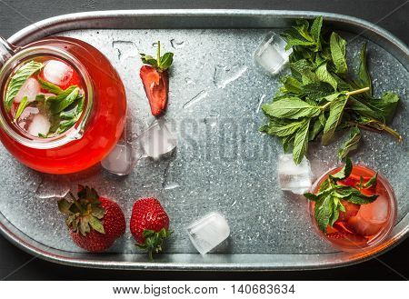 Homemade strawberry lemonade in glass and jug with mint and ice, served with fresh berries in metal tray, top view, horizontal composition