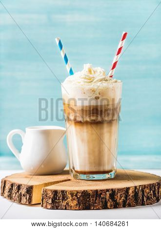 Latte macchiato with whipped cream in tall glass with two straws and pitcher on round wooden board over blue painted wall background, selective focus, vertical composition
