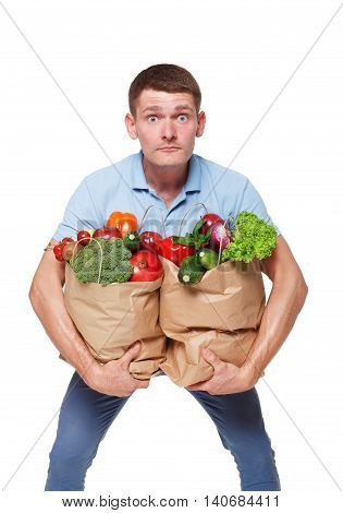 Surprised young man holding shopping bags full of groceries isolated at white background. Healthy food shopping. Paper package with vegetables and fruits, happy male buyer came from market