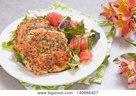 Healthy salmon quinoa kale burger with a green salad