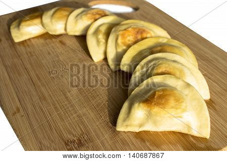 macro zoom of a polish pierogies assortment in a curve on a cutting board