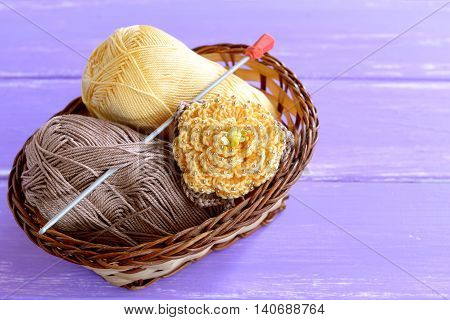 Yellow crochet flower with brown leaves and beads, hook, cotton yarn in wicker basket on lilac wooden background. Easy crochet flower ornament photo. Crafts for children women, beginners