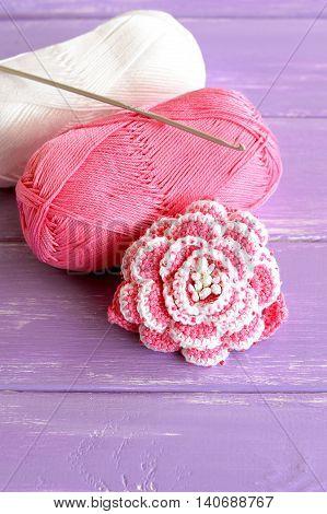 Home pink and white crochet rose two skeins of cotton yarn and crochet hook on lilac wooden background. Cute beaded flower pattern photo. Hand beautiful flower idea