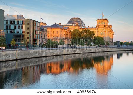 The Reichstag building (Bundestag) with reflection in river Spree early in the morning