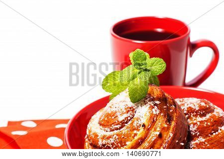 Two spiral tasty buns with coconut chips and mint and a cup of black coffee. Delicious breakfast sweet rolls and coffee. Coffee in red cup