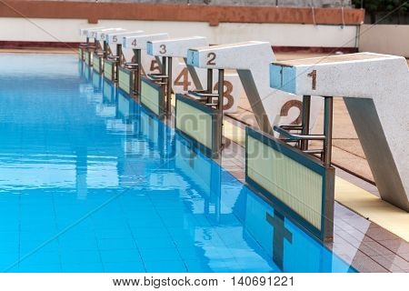 blue water wave in swimming pool reflects with sunlight blue tile ceramic to swimming race and water sports. selective focus.