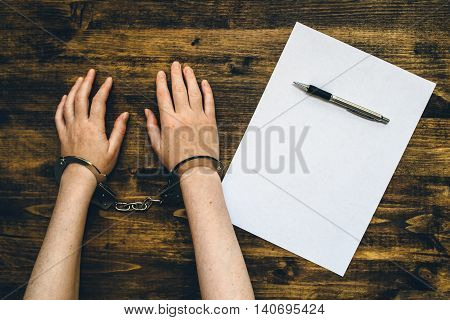 Female hands cuffed top view of police investigator detective desk with pencil and blank paper for statement