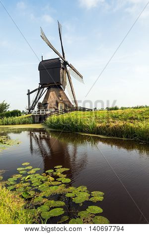 Wooden hollow post mill with a thatched under tower and a paddle wheel near the village of Molenaarsgraaf Alblasserwaard South Holland Netherlands. The now restored mill dates from about 1655 and is now a protected national monument.