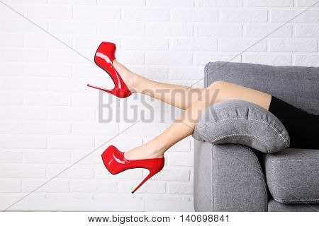 Female Legs With Red High Heels On Grey Sofa
