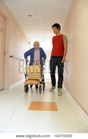 Male Nurse And Senior Woman With Walking Frame