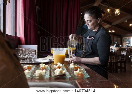 Tenerife, Spain, January 2015: Waitress pours fresh juice for customers on Bodega Monje- one of leading wine manufactures on north of Tenerife