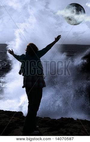 One Woman With Raised Hands Facing A Wave And Full Moon On Cliff Edge