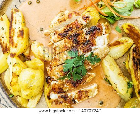 Tasty grilled chicken breast with american potatoes and herb butter. Food theme. One portion.