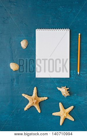 Notepad with blank page with pencil shells and starfish on blue surface top view. Summer background