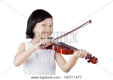Portrait of a cute Asian girl smiling at the camera while playing a violin in the studio isolated on white background