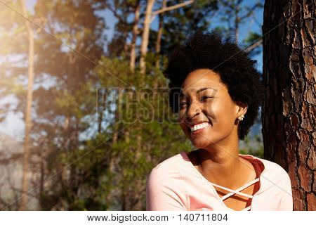 Cheerful Young African Woman Standing Near A Trees Outdoors