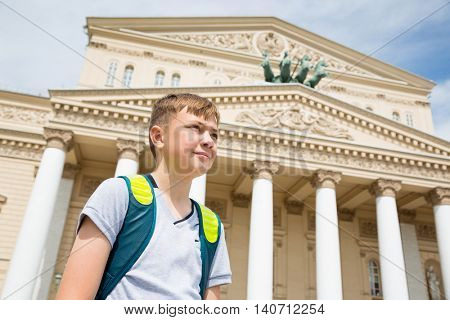 Russian boy stands on the background of the Bolshoi Theatre in Moscow
