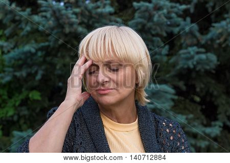 Elderly woman is having a headache and touching her head with her right hand