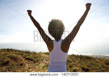 Young Woman Standing On Cliff With Her Hands Raised