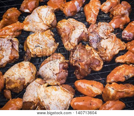 Close up image of chicken wings and fillets on a grate