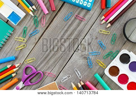 Frame with school supplies on gray wooden table. Top vie
